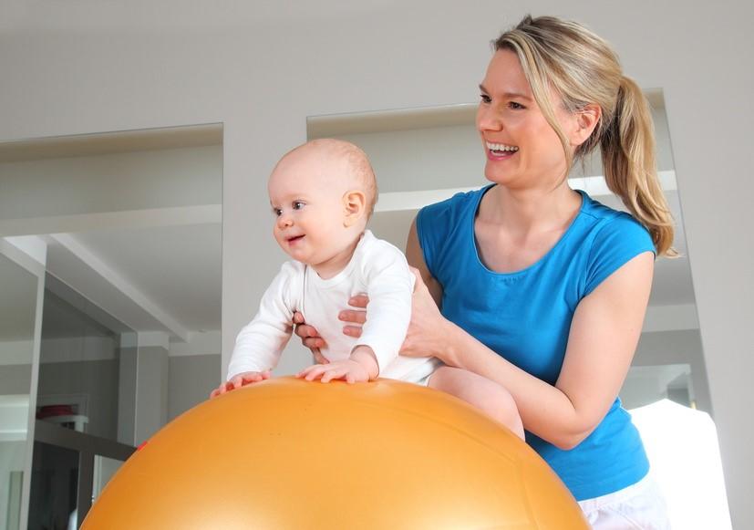 Übung für Babys zum Training der Bauchlage und der Rückenmuskulatur auf dem Ball