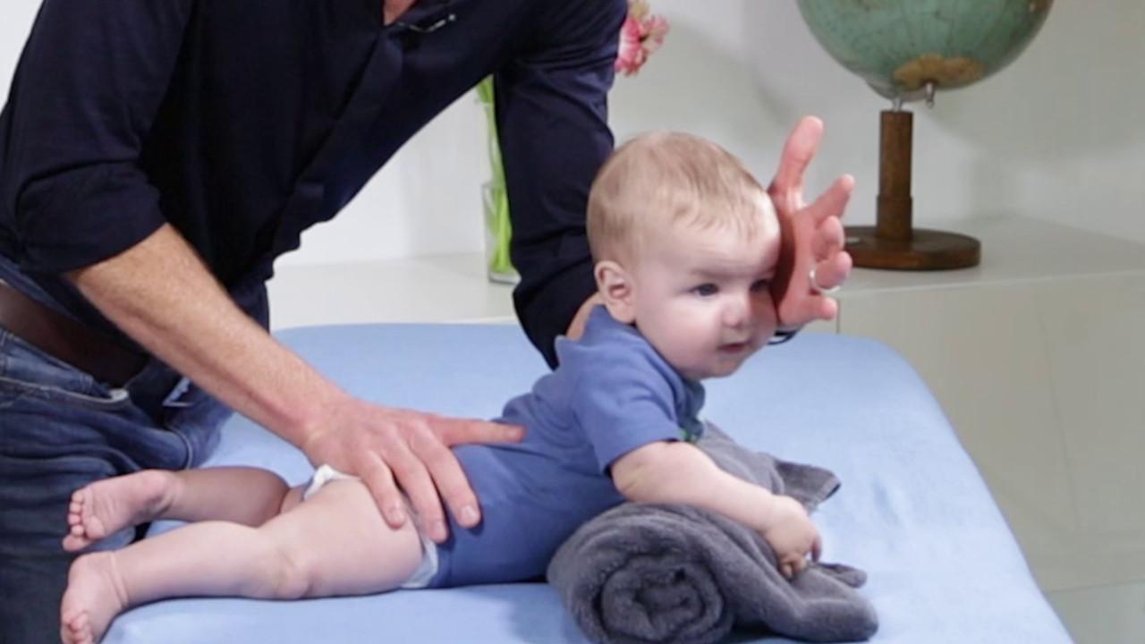 Training der Bauchlage im Säuglingsalter über einer Handtuchrolle